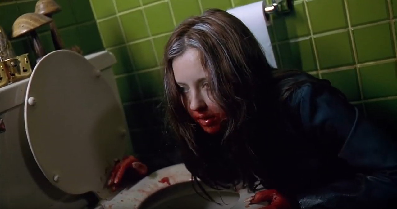 A still image taken from the horror film Ginger Snaps (2000). It shows a bloody woman clutching onto a toilet bowl.