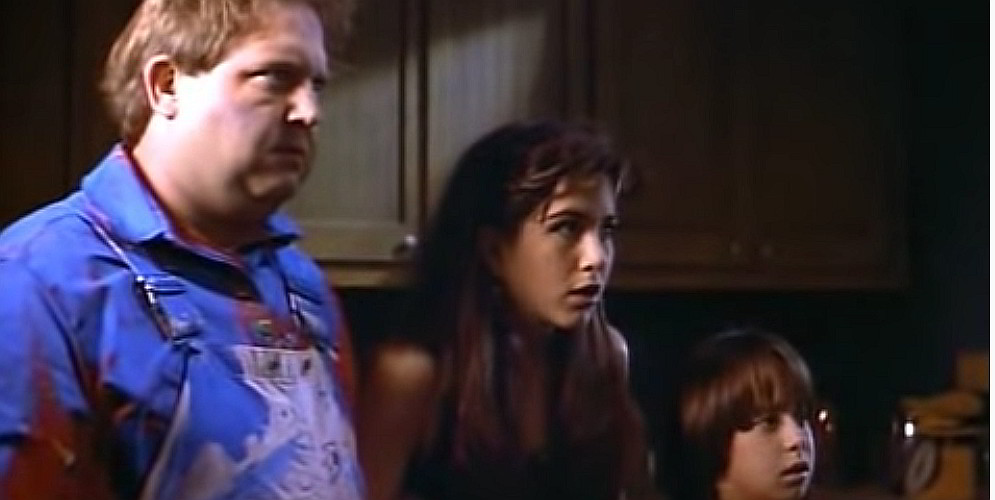 A still shot from the movie Leprechaun, showing Mark Holton, Jennifer Aniston, and Robert Hy Goldman.