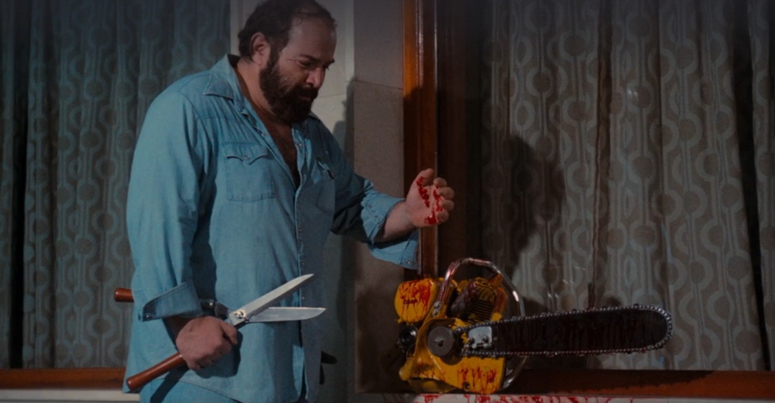 A still shot taken from the 1982 horror film Pieces. It shows a hulking man in pajamas standing over a bloody chainsaw.