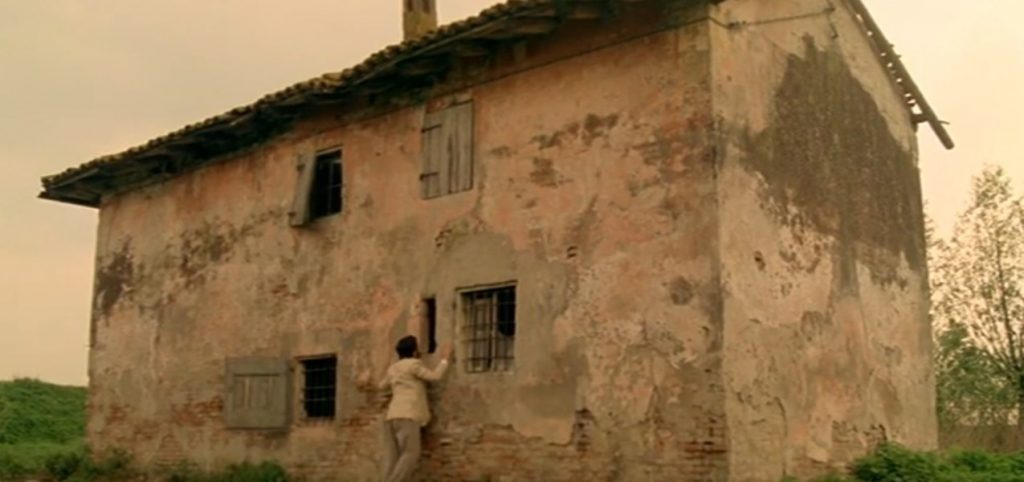 A screen shot taken from the film 'The House with Laughing Windows'. It shows a man standing in front of a dilapidated rural home.  Veniva dall'Italia: The Top 5 Essential Giallo Films