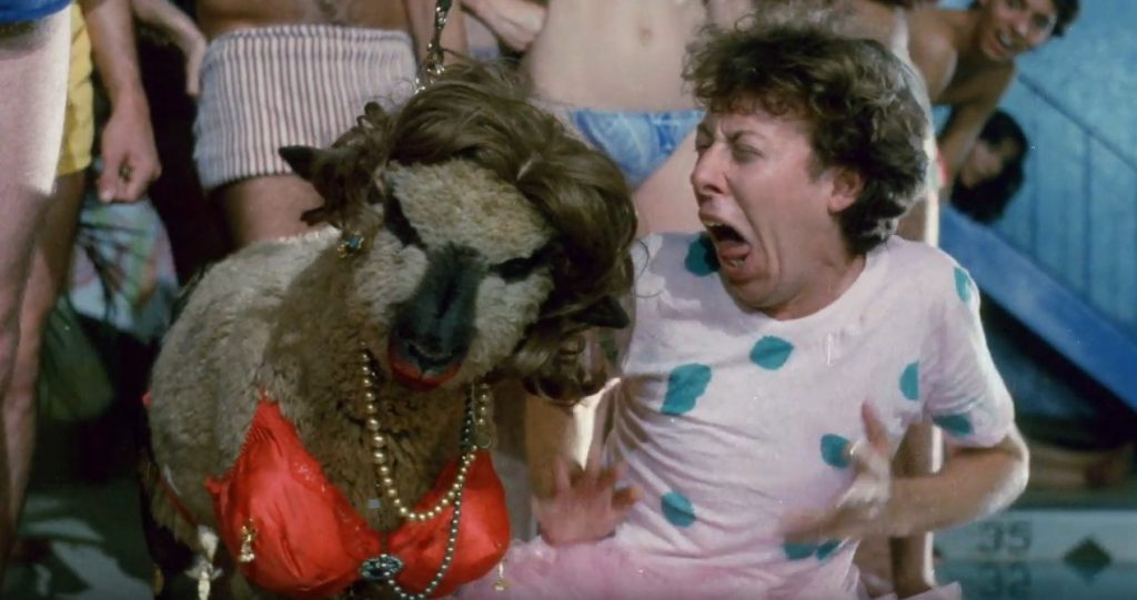 A screen shot taken from the film 'The Toxic Avenger'. It shows Mark Torgl's character, Melvin the Mop Boy, wearing a tutu because a sheep which has been made-up with a lipstick, a bra and a wig.  It's Troma Time! - Interview with Mark 'Melvin the Mop Boy' Torgl