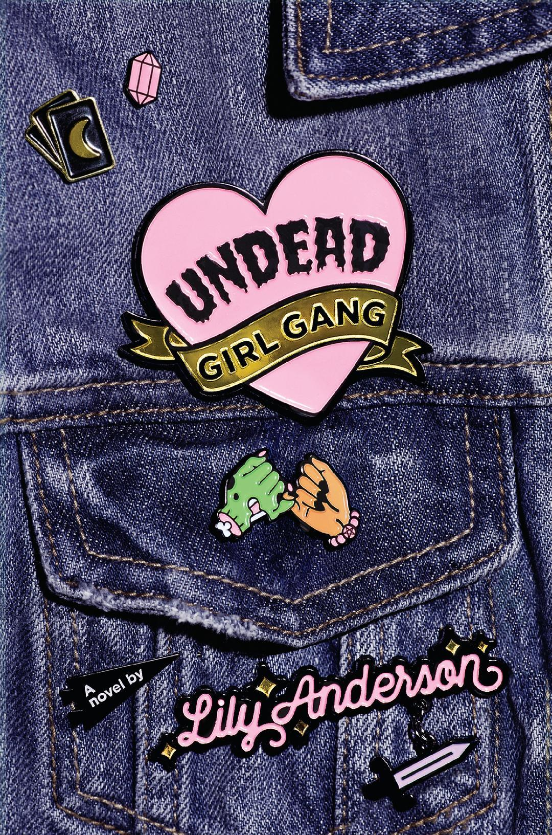 The cover of the book, which is a jean jacket with enamel pins.