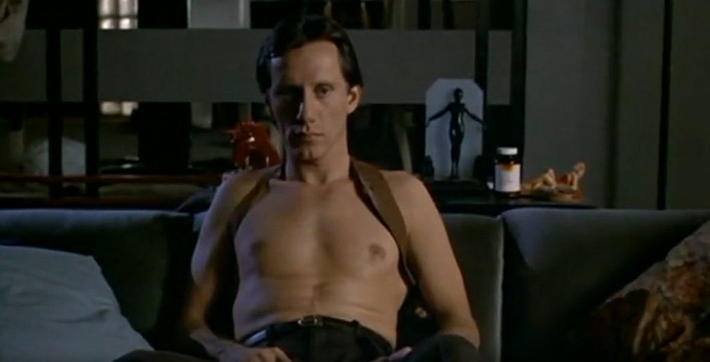 A screen shot taken from the 1983 horror film Videodrome. It shows James Woods as Max Renn, sitting shirtless on his couch and wearing a gun holster.   Canadian Classics: Videodrome (1983)