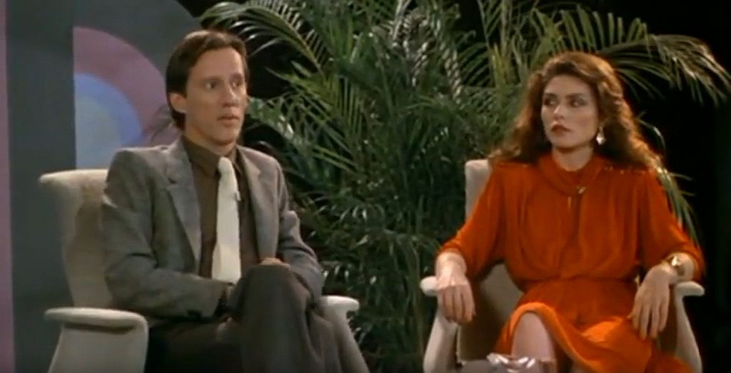 A screen shot taken from the 1983 horror film Videodrome. It shows James Woods' character Max Renn appearing on a talk show beside Debbie Harry's character Nicki Brand.  Canadian Classics: Videodrome (1983)
