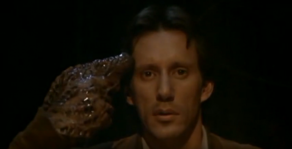 A screen shot taken from the 1983 horror film Videodrome. It shows James Woods' character Max Renn putting a fleshy, mutated gun to his head.