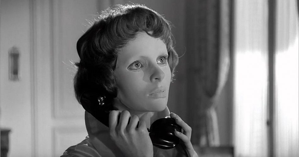 A screenshot taken from the 1960 french horror film 'Eyes Without a Face'. It shows the character, Christiane, holding a telephone receiver to her ear. Reviews in Retrospect: Eyes Without a Face (1960).