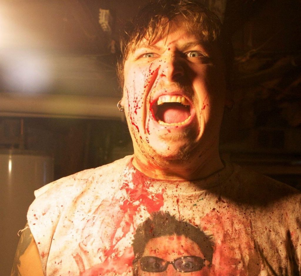 Fred Vogel as Peter Mountain, the lead character from the August Underground series. He is wearing a t-shirt with his own face on it and is covered in fake blood.  August in October: An Interview with Fred Vogel of TOETAG Pictures