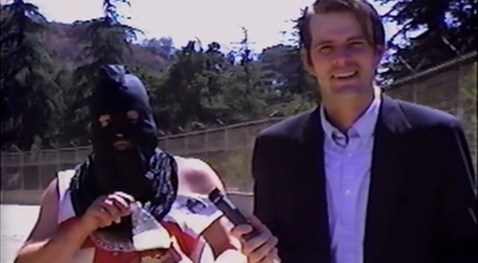 A screen capture taken from the documentary film The El Duce Tapes.  It shows Eldon 'El Duce' Hoke, drinking malt liquor behind a well-dressed man holding a microphone.  [ARROW EXCLUSIVE] 'The El Duce Tapes' is a Shocking Glimpse into a World of Sleaze