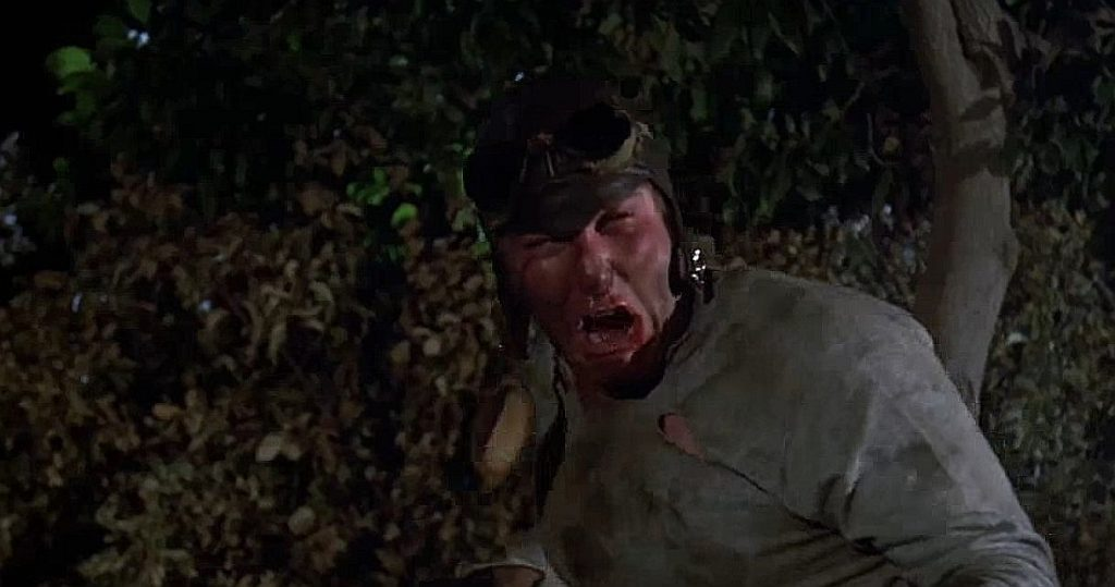 A screen shot taken from Friday the 13th, Part 5: A New Beginning (1985).  It shows Ron Sloan, as Junior Hubbard, pouting angrily on a motorbike with a bloodied nose.