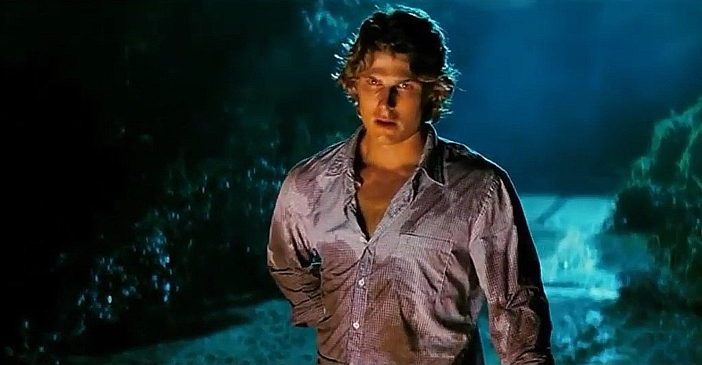 A screenshot taken from Friday the 13th (2009).  It shows Travis Van Winkle, as Trent Sutton, standing on an empty road at night.