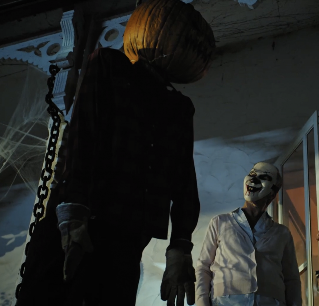 Web of Darkness S1E2 a scarecrow with a pumpkin head hangs from the porch as a woman with a sinister Halloween mask looks on