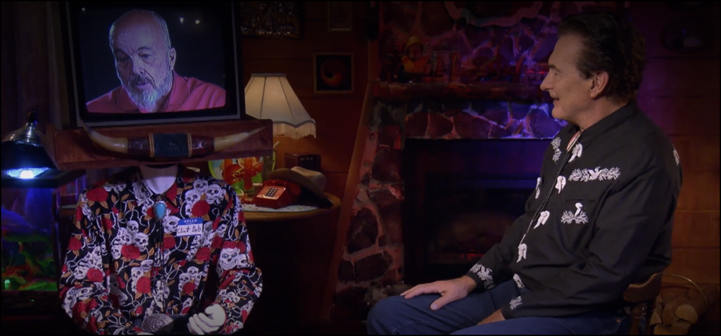 A screenshot from The Last Drive-In featuring Joe Bob and a virtual Clint Howard.