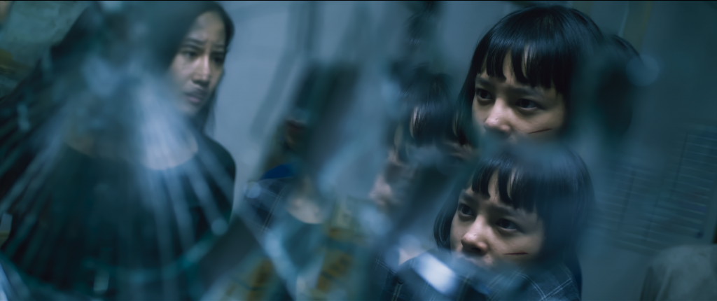 Picture of two teen women staring at a broken mirror. The Deep movie photo.