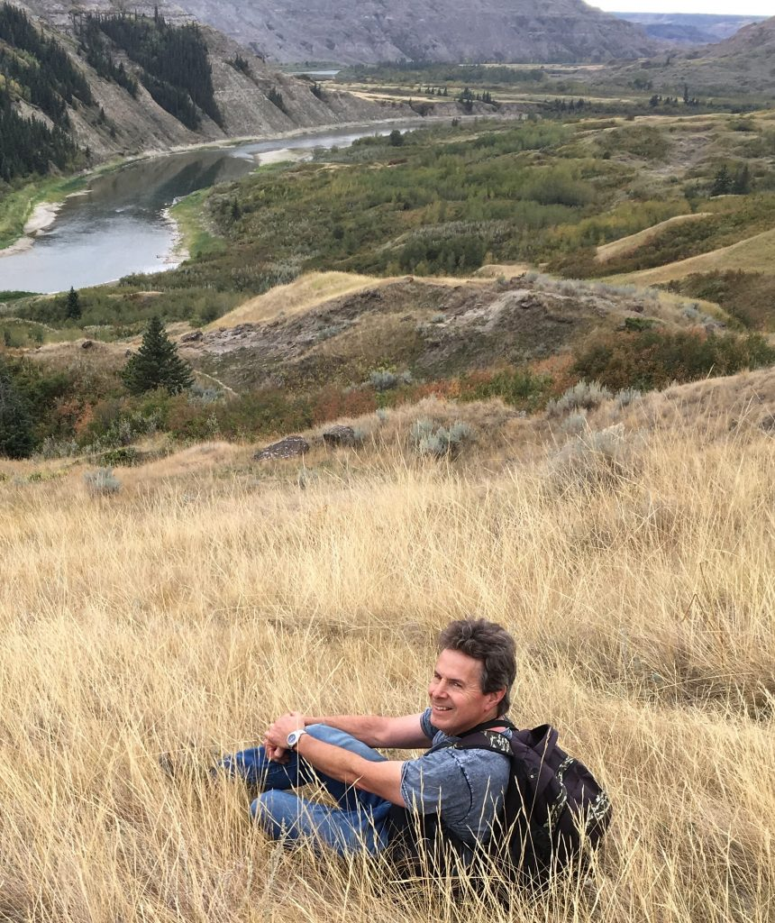 Picture of Greg Turlock over-viewing a river cutting through a mountainous forest.