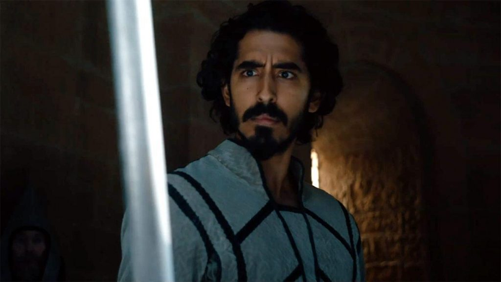 A still of Dev Patel holding Excalibur as Gawain from 2021's The Green Knight