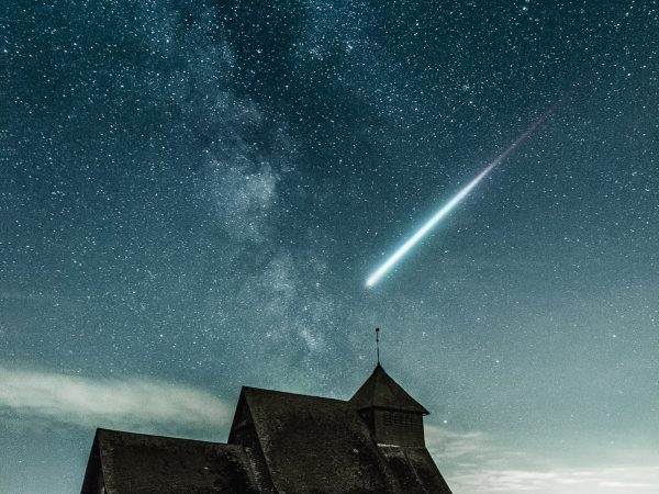 an old farmhouse with a meteor flying above it