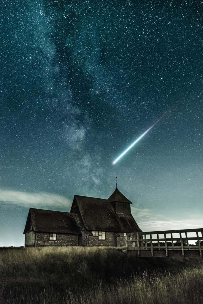 an old farm house with a meteor flying over it at night