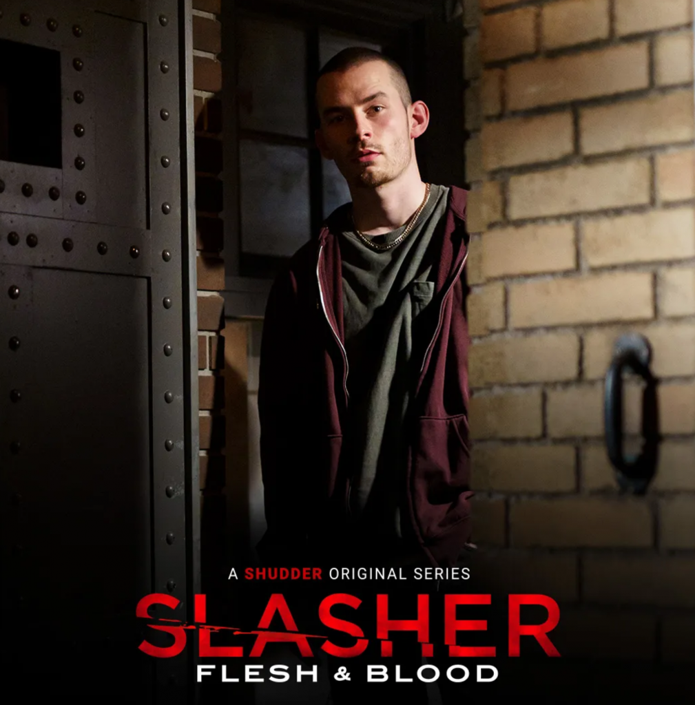 A man with a scruffy face and very short hair looks from behind a brick wall. Slasher S4E4