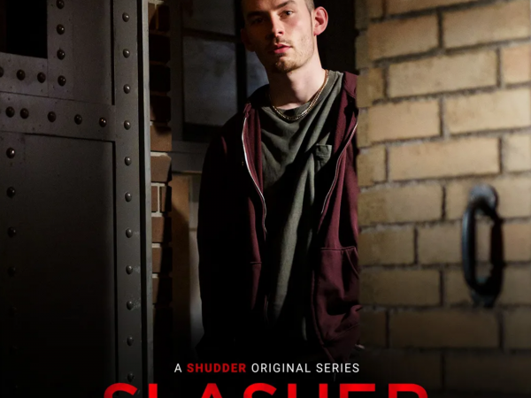 A scruffy looking man with very short hair peaks out from behind a brick wall. Slasher S4E4