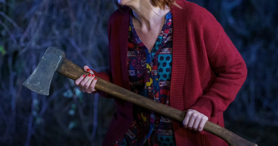 Crazy looking woman wearing a Mr Rogers type sweater as she runs around the forest with an axe. S4E5